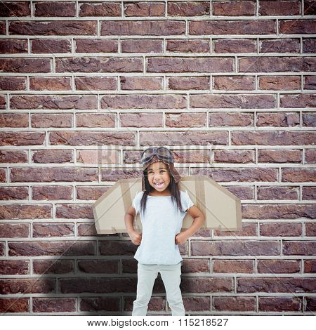 Standing girl with fake wings pretending to be pilot against red brick wall