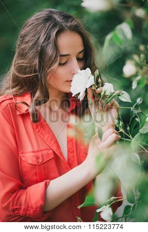 Young woman posing in a rose garden