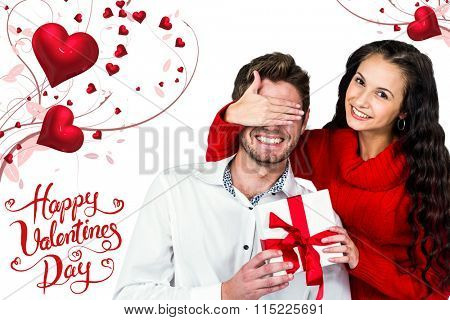 Young woman covering eyes of partner holding gift against happy valentines day