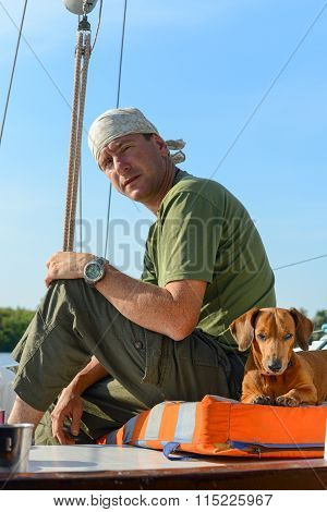 Yachtsman Travels With His Dog On An Old Sailboat.