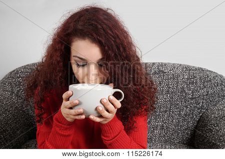 girl sipping from large cup of coffee