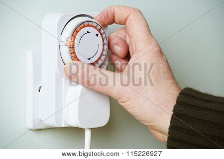 Man Adjusting Timer On Electrical Socket