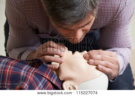 Man In First Aid Class Performing Mouth To Mouth Resuscitation On Dummy