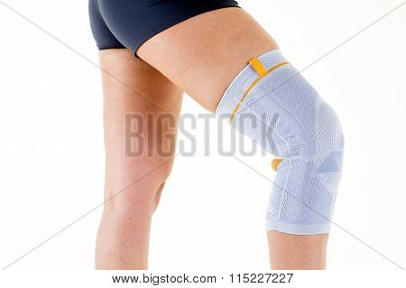 Woman Wearing Flexible Knee Brace In White Studio