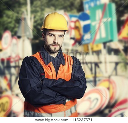 Worker In Protective Uniform In Front Of Road Signs