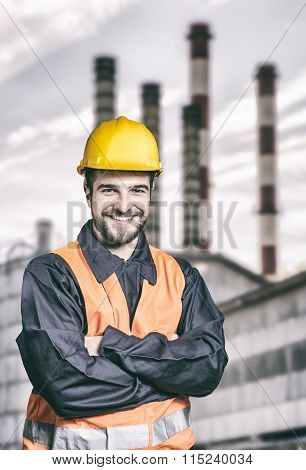 Smiling Worker In Protective Uniform In Front Of Industrial Chimney