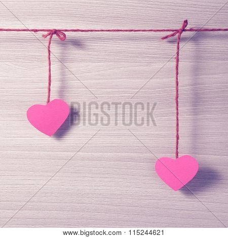 Two paper hearts hanging on a rope.