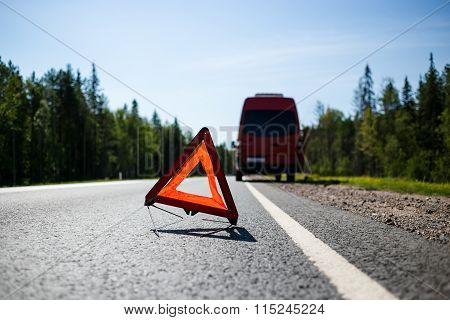Red warning triangle with a broken down minibus car