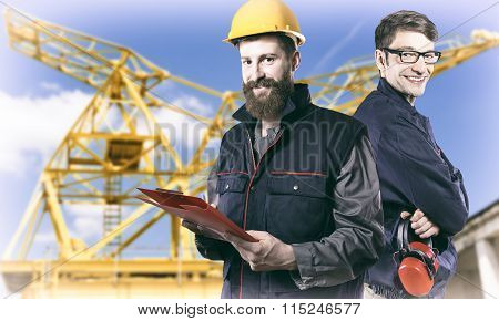 Smiling Workers In Protective Uniforms In Front Of Construction Crane