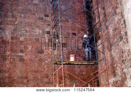 Construction Worker On Scaffolding Working On Textured Wall