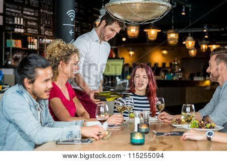 Young waiter serving wine to customers at table in restaurant