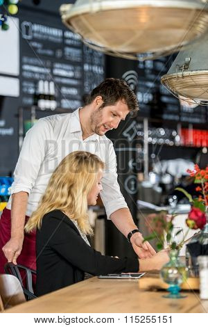 Young waiter discussing menu with female customer at table in cafe