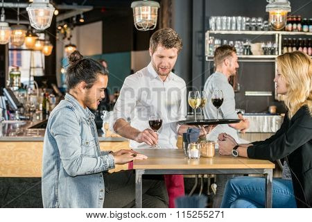 Young waiter serving wine to customers at table in bar