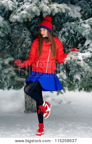 Attractive Young Woman In Wintertime Outdoor. The Girl In A Red Jacket And Blue Skirt Standing Under