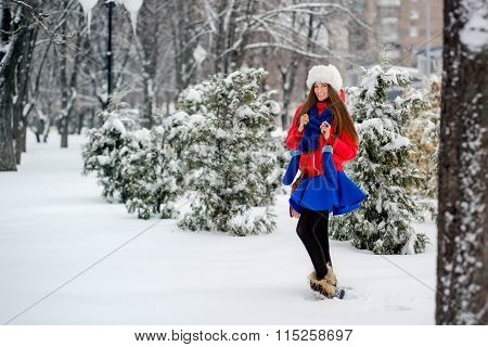 Beautiful Winter Portrait Of Young Woman In The Winter Snowy Scenery. The Girl In A White Fur Hat, A