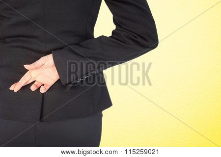 Businesswoman with fingers crossed behind her back against grey wall