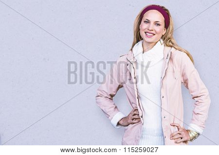 Smiling woman with hands on hips in front of window against path
