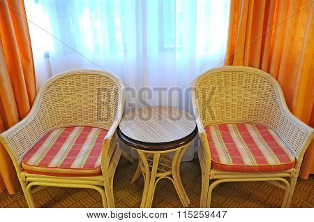 Rattan Relax Chairs And Round Table Near The Window