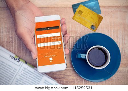 Credit Card against person using smart phone by coffee and document on table