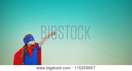 Masked girl pretending to be superhero against blue green background