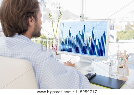 Desinger working on his computer against blue data