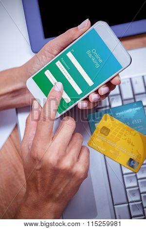 Credit Card against feminine hands using smartphone