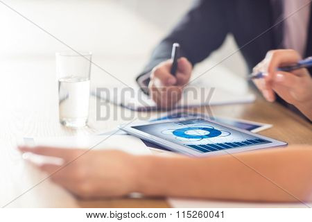 Blue data against business people using tablet