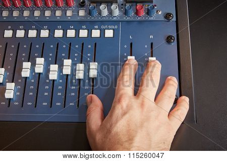 Pushing The Faders On A Mixing Desk