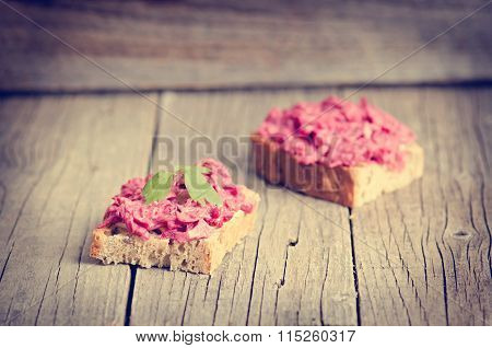 Two slices of bread on a wooden table with beetroot spread. Natural background and healthy
