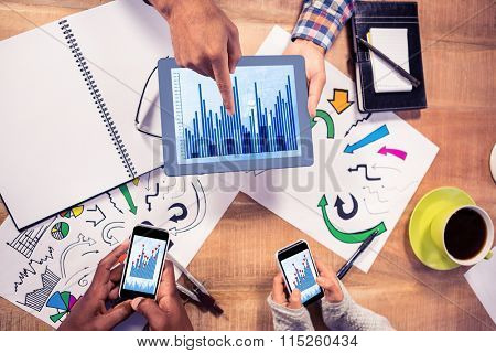 Blue data against overhead view of creative business team working at desk