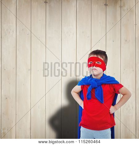 Masked boy pretending to be superhero against wooden planks