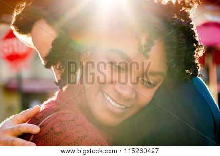 Happy young african woman hugging man in a bright sunny day. Close up face of young girl embracing her boyfriend and smiling with closed eyes. Romantic happy couple hugging outdoor.