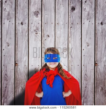 Masked girl pretending to be superhero against digitally generated grey wooden planks