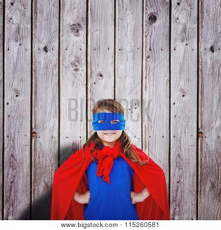 Masked girl pretending to be superhero against digitally generated grey wooden planks