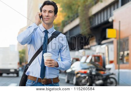 Happy businessman talking on the mobile phone. Young businessman communicating over cell phone while holding a paper cup and walking on the road. Smiling guy at smart phone while going to work.
