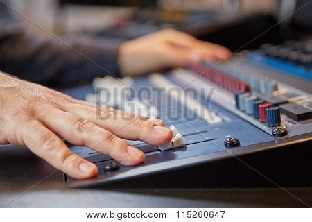 Mixing Engineer Moving The Sliders Of Audio Console