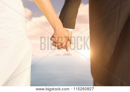 Close up of cute young newlyweds holding their hands against calm sea with lighthouse