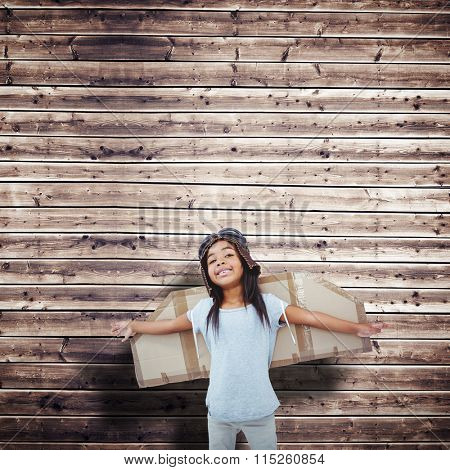 Girl with fake wings pretending to be pilot against wooden planks background
