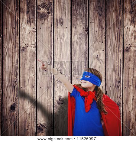 Masked girl pretending to be superhero against wooden planks background