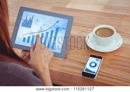 Blue data against over shoulder view of hipster woman using tablet