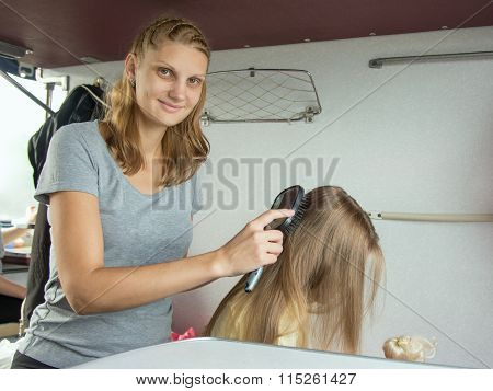 Mother Combing Daughter's Long Hair On A Cot In A Train