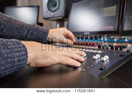 Side View Of Hands Of Audio Engineer Mixing On Console