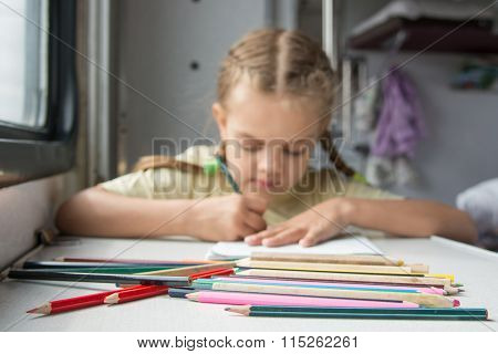 Pencils In The Foreground, In The Background A Six Year Old Girl Drawing Pencils In A Second-class T