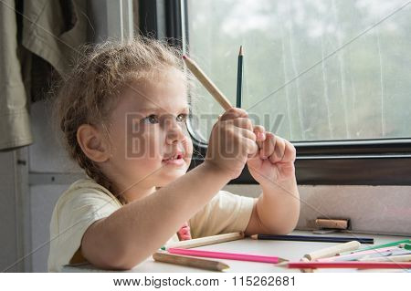 Girl Looks Funny On Pencils At The Table In The Second-class Train Carriage