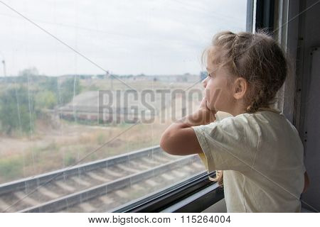 The Girl Sadly Looking Out The Window Of A Train Car