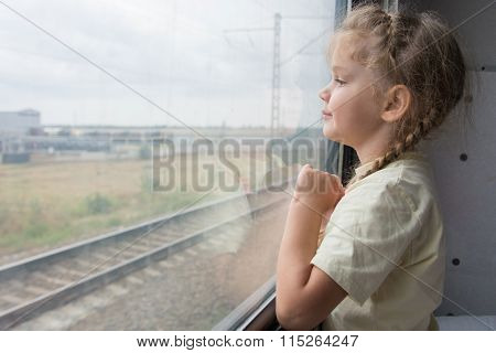Four-year Girl Looks Out The Window Of The Train Car