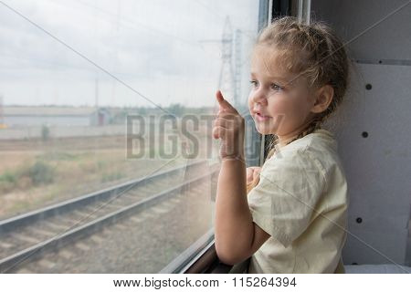 Four-year Girl Shows A Finger On Something From The Window Of A Train Car