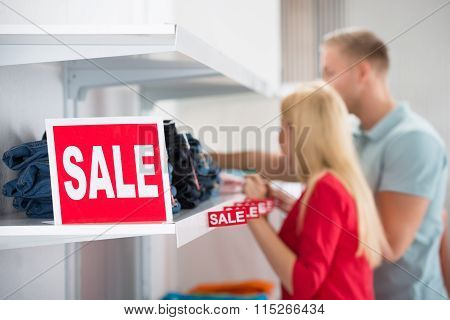 Couple Looking At Sale Tag On Jeans