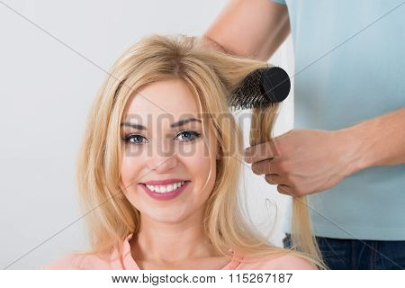 Hairstylist Brushing Woman's Hair At Salon