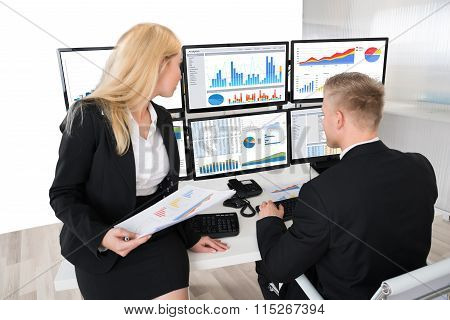 Financial Workers Analyzing Graphs On Computers In Office